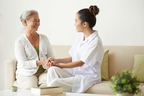 Bildet viser en kvinnelig tannlege som beroliger sin redde pasient. Beroligende samtaleterapi er viktig for deg som har tannlegeskrekk.