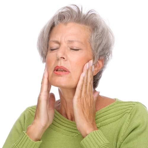 Bildet viser en kvinne som holder hendene på kjeveleddene pga smerte. Bitt og kjeveleddsbehandling kan utføres med bittskinne.