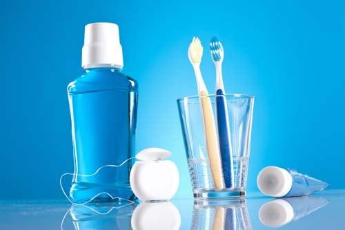 Dette er et bilde på 2 tannbørster i et glass med fluor-munnskyll, tannkrem og tanntråd ved siden av glasset. Forebyggende tannbehandling er en del av vårt behandlingsprogram.
