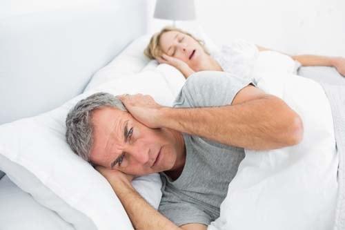Bildet viser et par i sengen der kvinnen snorker og mannen holder for ørene.