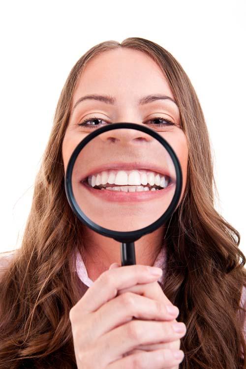 Bilden visar en kvinna som håller ett förstoringsglas framför munnen.