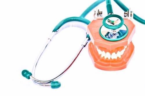 Bildet viser et stetoskop som ligger over en kjeve. Vi tilbyr behandingsgaranti for visse tannbehandlinger upp til 2 år.