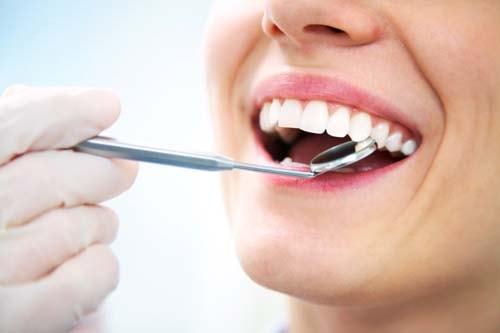 Bilden visar vita och raka tänder där behandlaren håller en dentalspegel vid tänderna.
