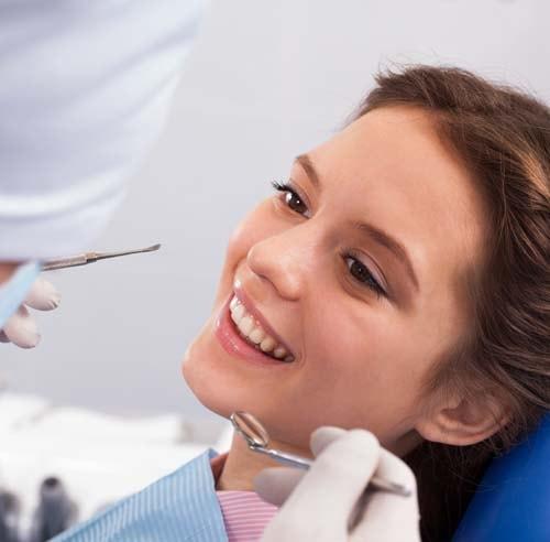 Bildet viser en jente som sitter i tannlegestolen med smil på leppene. Første gang hos tannlegen er en viktig steg for deg som har tannlegeskrekk.