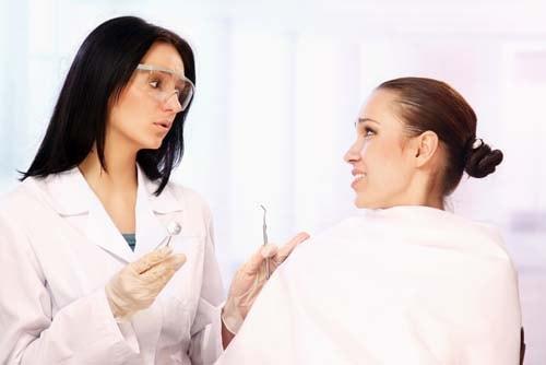 Bilden visar en kvinnlig tandläkare som försöker lugna ner sin rädda patient.