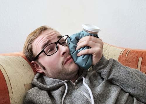 Bildet viser en person (mann) med tannverk der han holder en ispose på kinnen. Vi tlbyr tannlegevakt ved akutt tannverk.